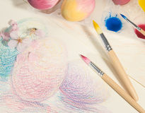 Easter hand-painted eggs with painter brushes,watercolors and almond blossom,arranged on a colored drawing. Royalty Free Stock Photography