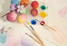 Easter hand-painted eggs with painter brushes,watercolors and almond blossom,arranged on a colored drawing. Royalty Free Stock Images