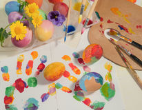 Easter hand-painted eggs with painter brushes,wooden palette,watercolors and spring flowers,arranged on colored fingerprints. Stock Image