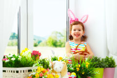 Easter. happy child girl with bunny ears and colorful eggs sitti Stock Photography