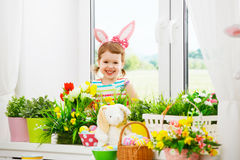 Easter. happy child girl with bunny ears and colorful eggs sitti Stock Photos