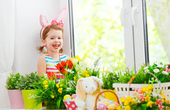 Easter. happy child girl with bunny ears and colorful eggs sitti Royalty Free Stock Photos