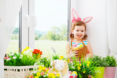Easter. happy child girl with bunny ears and colorful eggs sitti Stock Image