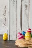 Easter is so happy time!. Decoration with colorful easter eggs, greetings in german, wood planks in the background Royalty Free Stock Photos