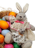 Easter hares in a basket. With colored eggs on white background Royalty Free Stock Images