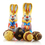 Easter hares with chocolate eggs. Easter hares with chocolate isolated over white Stock Images