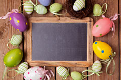 Easter holiday background with chalkboard and eggs decorations Stock Photography