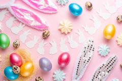 Easter holiday background. Easter eggs colored with rabbit ears on a pink background with sweets. Flat lay, horizontal composition. Greeting card concept stock images