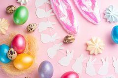 Easter holiday background. Easter eggs colored with rabbit ears on a pink background with sweets. Flat lay, horizontal composition. Greeting card concept stock image