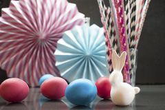 Easter holiday background with eggs, porcelain bunny and paper decoration stock photography
