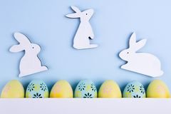 Easter holiday background with eggs. Top view of colorful painted chicken eggs plased in a row and decorative bunny. Easter holiday background with eggs. Top stock photography