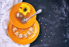 Easter holiday background, orange plate, golden eggs Stock Photography