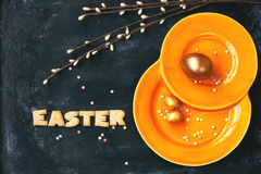 Easter holiday background, orange plate, golden eggs Royalty Free Stock Images