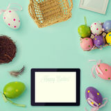 Easter holiday background with retro filter effect. Easter eggs decorations and tablet. View from above Stock Image