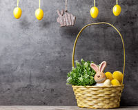 Easter holiday basket with a bunny, eggs and flowers Stock Image