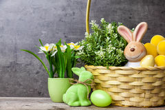 Easter holiday basket with a bunny, eggs and flowers Stock Photo