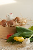 Easter holiday basket with eggs, flowers and easter bunny on rustic wooden. Easter rabbit with eggs tulips stock image