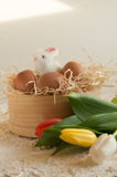 Easter holiday basket with eggs, flowers and easter bunny on rustic wooden Stock Photos