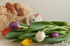 Easter holiday basket with eggs, flowers and easter bunny on rustic wooden Royalty Free Stock Photos