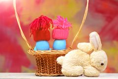 Easter holiday, blue smurfs eggs in hats in basket, rabbit. Happy easter egg easter blue eggs as smurfs in winter hats red and pink color in straw basket and Stock Images