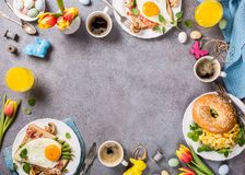 Easter holiday breakfast flat lay. Easter breakfast flat lay with scrambled eggs bagels, orange tulips, bread toast with fried egg and green asparagus, colored Stock Photo