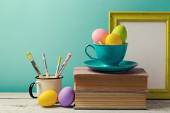 Easter holiday celebration with handmade painted eggs in coffee cup, books and brushes. Creative workplace Stock Photography