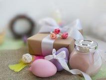 Easter eggs, gift box, cream jar on burlap fabric on blurred background. stock image