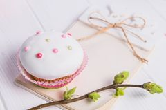 Easter holiday composition of decorated cupcake, branch with young shoots of greenery and handcraft notebook with empy blank on wo. Oden background. Art concept Royalty Free Stock Photos