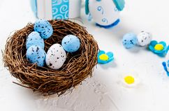 Easter holiday composition of decorative eggs. Easter decorative white and blue eggs in a nest and two toy chickens in blue on a white background , Holidays royalty free stock photos
