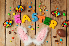Easter holiday concept with chocolate eggs and bunny ears on wooden background. Royalty Free Stock Images
