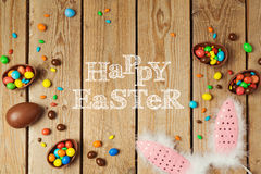 Easter holiday concept with chocolate eggs and bunny ears on wooden background. Top view from above Stock Images