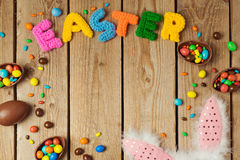 Easter holiday concept with chocolate eggs and bunny ears on wooden board background. Top view from above Stock Images