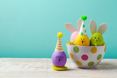Easter holiday concept with cute handmade eggs, bunny, chicks and party hats in bowl. On wooden table stock photos