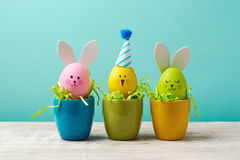 Easter holiday concept with cute handmade eggs, bunny, chicks and party hats in cup Stock Images