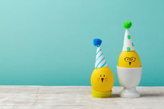 Easter holiday concept with cute handmade eggs chicks over blue retro background Stock Photos