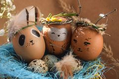 Easter holiday concept with cute handmade eggs, rabbit, chicks, owl, panda and deer. Creative eggs for Easter. Happy easter stock photography