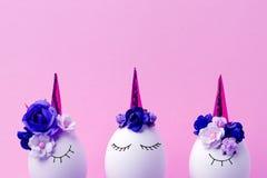 Easter holiday concept with cute handmade eggs, set of kawaii cute sleepy unicorns eggs, trendy neon disco pink background.  stock photo