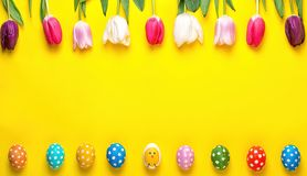 Easter eggs with colorful tulips on yellow background. Easter holiday concept. Easter holiday concept.Easter eggs with colorful tulips on yellow background stock images