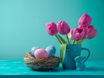 Easter holiday concept with tulip flowers. Eggs decoration in bird nest and bunny Stock Image