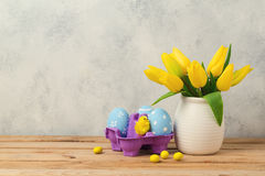 Easter holiday concept with tulip flowers and eggs on wooden table Royalty Free Stock Images