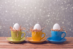 Easter holiday creative background with eggs in coffee cups Royalty Free Stock Image