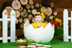 Easter holiday. A cute little girl in a duck suit hatched from a big egg. In the background a wooden stumps. Horizontally framed shot royalty free stock photography