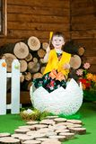 Easter holiday. A cute little girl in a duck suit hatched from a big egg. In the background a wooden stumps. Vertically framed shot stock images