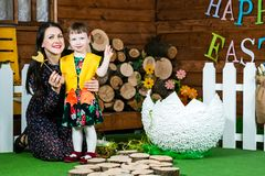 Easter holiday. A cute little girl in a duck suit hatched from a big egg. Mom hugs her daughter. On wall writing Happy Easter. Horizontally framed shot royalty free stock photo