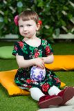 Easter holiday. Cute little girl holding an easter egg. Ivy wall in background stock image