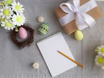 Easter holiday decorated eggs, blank paper notepad on grey background stock photos