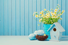 Easter holiday decoration with daisy flowers, eggs and birdhouse. Over blue background Stock Photo