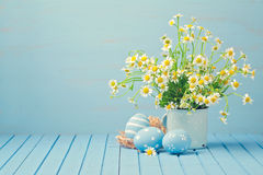 Easter holiday decoration with daisy flowers and painted eggs. On wooden blue table Royalty Free Stock Image
