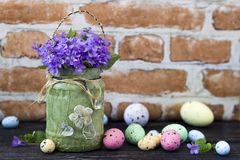 Easter eggs and violet bouquet in front of brick wall Royalty Free Stock Images
