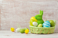 Easter holiday decorations with eggs and bunny in basket over wooden background Royalty Free Stock Images